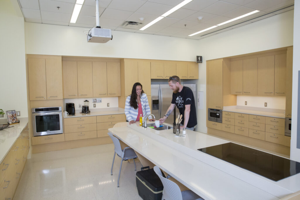 Center kitchen with two students standing and conversing around the kitchen sink.  The kitchen is ADA accessible, with wide spaces low hanging cabinets.