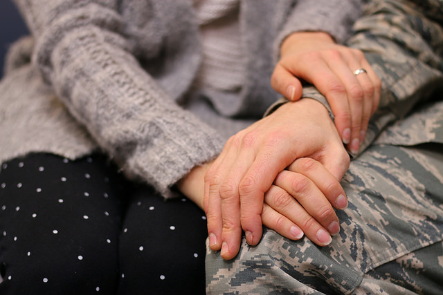 Two people's hands embracing.
