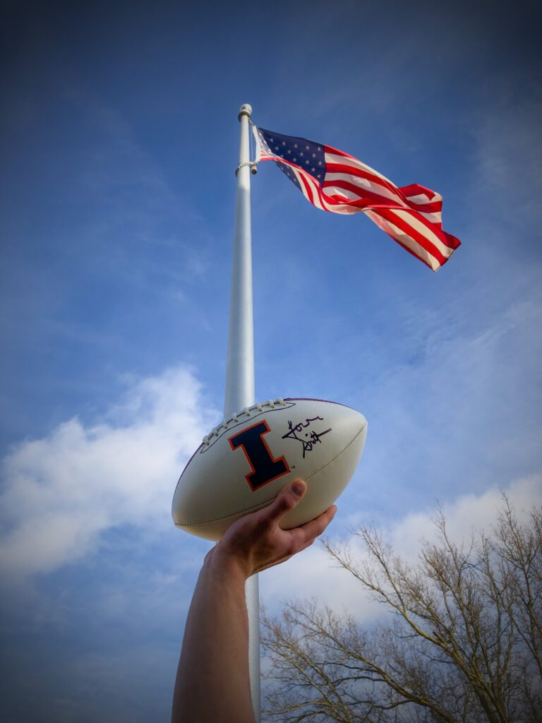 American Flag on flag pole with a persons hand holding a white football with an Illini I on it, signed by Lovie Smith.