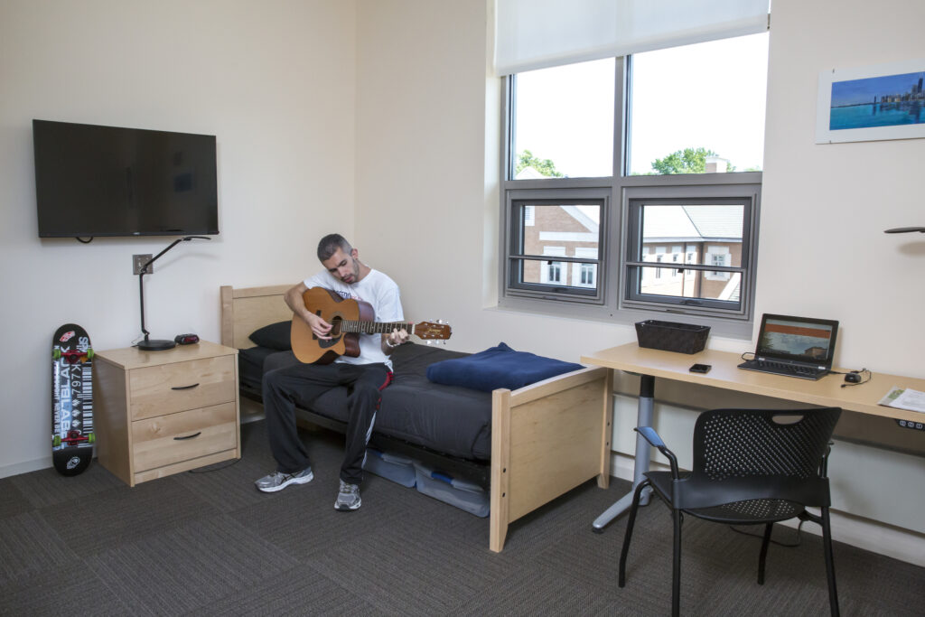 Center resident room with resident pictured playing guitar.  Room has a television on the wall, side table, twin size bed, window, and adjustable desk.
