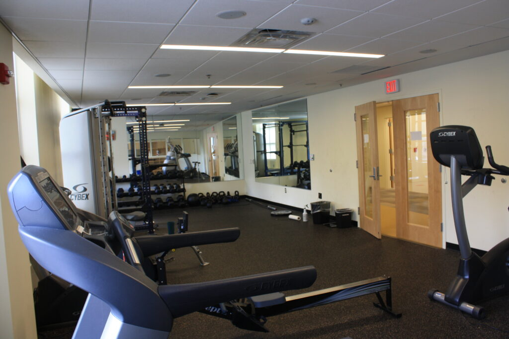 Center gym with dumbbells', squat bench, ellipticals, and treadmills.