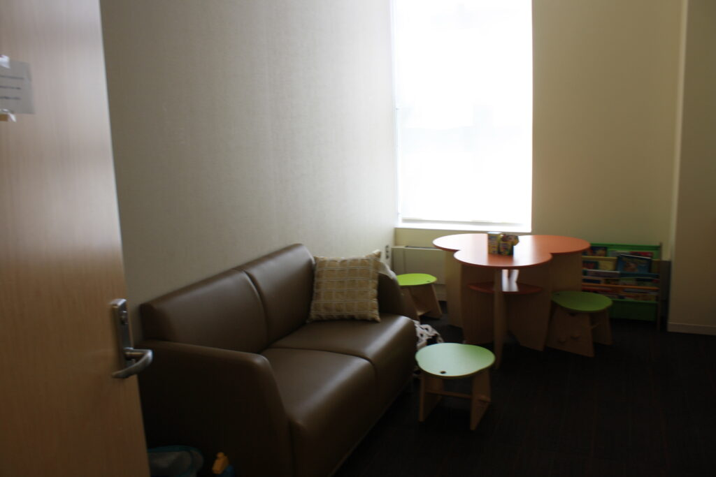 Waiting room in counseling wing with sofa and child table.