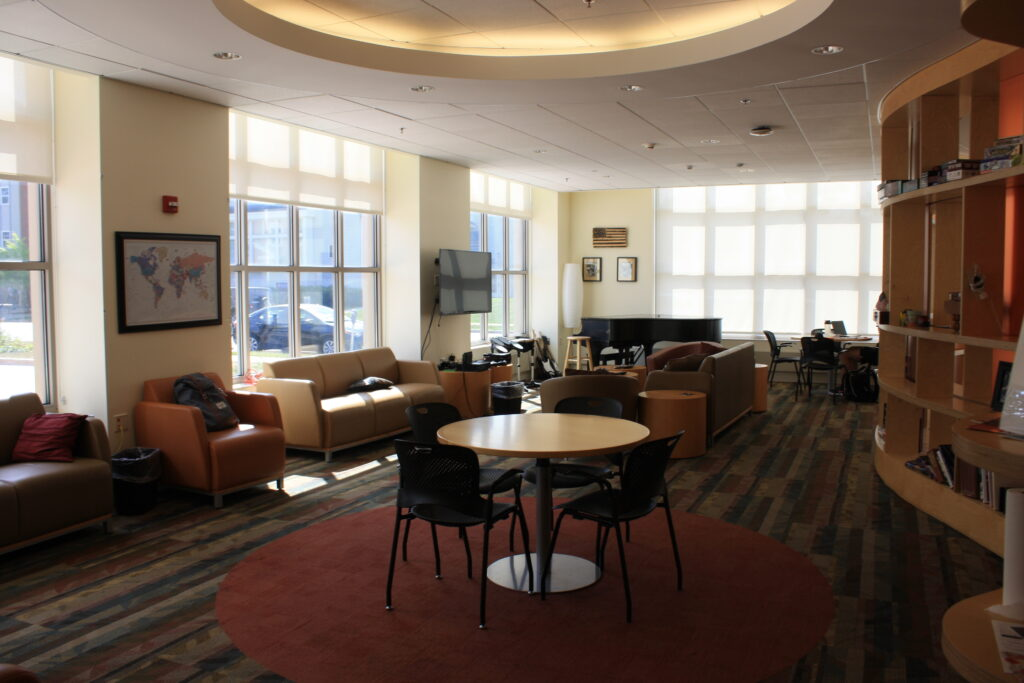 Lounge area at the Chez Veterans Center.  Couches a line wide windows, tables with chairs are spread around.  A book shelf separates the lounge and kitchen/dining area.