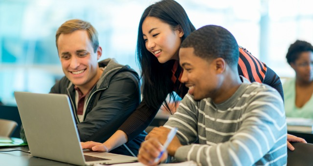 Three students surrounding a laptop, all smiling looking at the screen.  One of the students is slouched over the laptop.