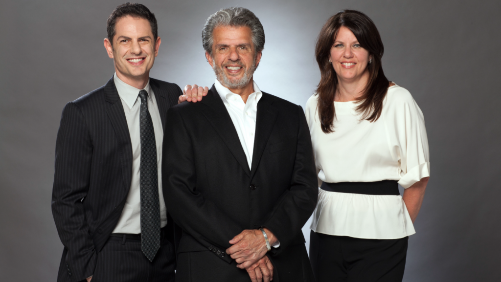 Image of Chez Family posing for the picture with a gray background.  Eric Chez is pictured on the left, has black hair, is wearing a stripped black suit with a gray collared shirt and black spotted tie; he has his left hand on Ron Chez.  Ron is in the middle of the group and is wearing a black suit and white collared shirt.   Ron has gray hair and gray facial hair.  Elizabeth Chez is to the left of Ron Chez and has a white shirt with a black belt and black dress pants.  Elizabeth has brown hair.