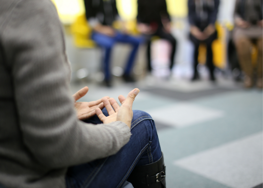 Blurred background with several people sitting in group.  Clear image of hands open on lap of someone that appears to be facilitating a conversation.