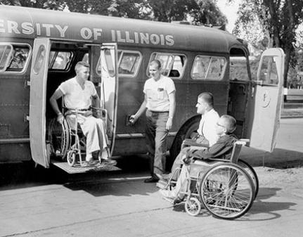Two men in wheel chairs looking at one man in wheel chair being lifted down wheelchair accessible bus.  Another man stands next to ramp, lowering ramp.  Image is in black and white.