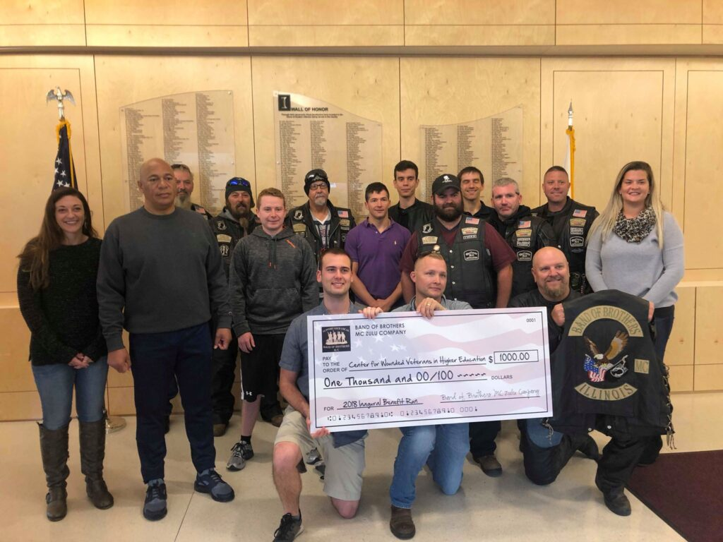 Band of Brothers Motorcycle Group members crowd around students and staff with a large check from their donations to the Center.